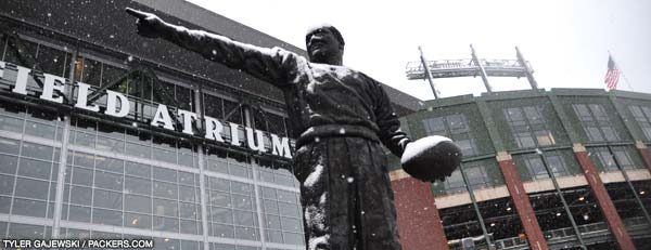 The statue of Curly Lambeau in front of his namesake Atrium accumulates snow Sunday afternoon