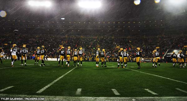 The Green Bay Packers take to the field for warmups as snow falls from above