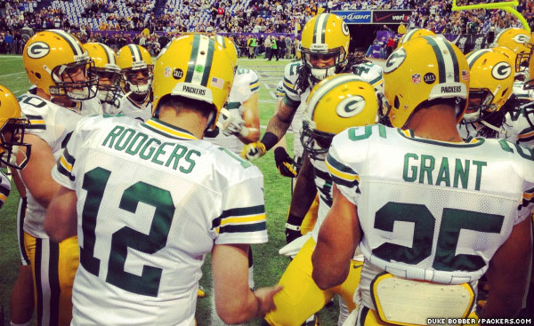 Aaron Rodgers, Ryan Grant and other look on as Erik Walden dances in a pre-game team huddle