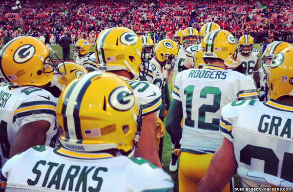 The Packers huddle up on the field before the game