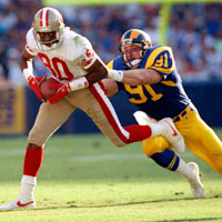 Los Angeles Rams LB Kevin Greene tackles San Francisco 49ers WR Jerry Rice in a 1992 game.